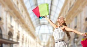 Lycklig kvinna med shoppingpåsar över galleria arkivfoton