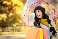 Lycklig kvinna med shoppingpåsar i höst Arkivbilder