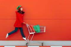 Lycklig kvinna med shoppingvagnen som är klar för jul Sale arkivfoto