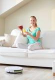 Lycklig kvinna med smartphonen som hemma dricker te Arkivbild