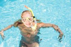 Lycklig kvinna med snorkelkugghjulsimning i pöl Arkivbilder