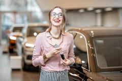 Lycklig kvinna med tangenter i bilvisningslokalen royaltyfri foto