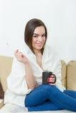 Lycklig kvinna med termometern som läkas av förkylningar Fotografering för Bildbyråer
