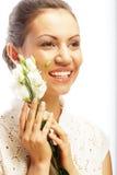 Lycklig kvinna med vita blommor som isoleras på vit Fotografering för Bildbyråer