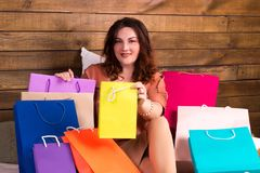 Lycklig kvinna, når att ha shoppat med färgglade pappers- påsar på säng Royaltyfri Foto