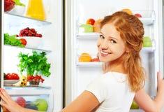 Lycklig kvinna och öppet kylskåp med frukter, grönsaker och honom arkivbilder