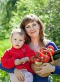 Lycklig kvinna och barn med   grönsaker Arkivbild
