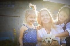 Lycklig kvinna och hennes döttrar med valpen av labrador Arkivbild