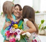 Lycklig kvinna och hennes lilla döttrar i vardagsrummet Royaltyfria Foton
