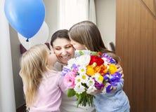 Lycklig kvinna och hennes lilla döttrar i vardagsrummet Royaltyfri Bild