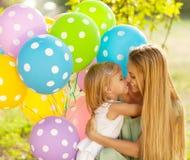 Lycklig kvinna och hennes lilla döttrar med ballons utomhus Royaltyfri Bild