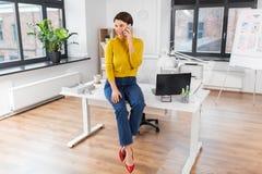 Lycklig kvinna och kalla p? smartphonen p? kontoret royaltyfri fotografi