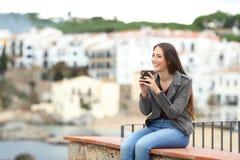 Lycklig kvinna på en avsats som bort dricker och ser royaltyfria bilder