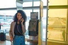 Lycklig kvinna på flygplatsen som talar vid den offentliga telefonen Royaltyfria Foton