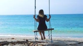 Lycklig kvinna på gunga på havsstranden Ung flicka som svänger på semester för sommar för strandgungastund Ha gyckel på sommar stock video