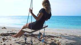 Lycklig kvinna på gunga på havsstranden Ung flicka som svänger på semester för sommar för strandgungastund Ha rolig tropisk ferie stock video