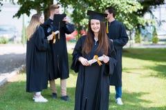 Lycklig kvinna på hennes universitet för avläggande av examendag Utbildning och peop royaltyfri foto