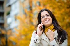 Lycklig kvinna på mobiltelefonen som är utomhus- i höst royaltyfri fotografi