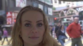 Lycklig kvinna p? modern stadsgatabakgrund som ser till kameran N?tt kvinna f?r framsida med fr?knar som ler och poserar fr?n arkivfilmer