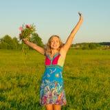 Lycklig kvinna på naturen med blommor Royaltyfri Foto
