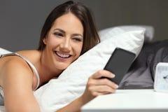 Lycklig kvinna på sängen som kontrollerar telefonen i natten royaltyfri fotografi