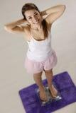 Lycklig kvinna på scales som tillfredsställs för viktförlust Arkivbilder