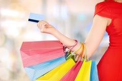Lycklig kvinna på shopping med påsar och kreditkortar, julförsäljningar, rabatter