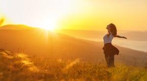 Lycklig kvinna på solnedgång i öppna händer för naturiwith Arkivbilder