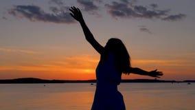 Lycklig kvinna på solnedgången till stranden som lyfter upp hennes armar och omkring vänder arkivfilmer