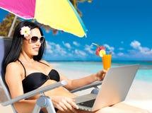 Lycklig kvinna på stranden med en bärbar dator Royaltyfri Fotografi