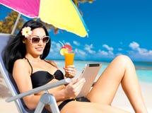 Lycklig kvinna på stranden med ipad Fotografering för Bildbyråer