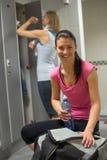 Lycklig kvinna på idrottshalls omklädningsrum med låsbara skåp Royaltyfria Bilder