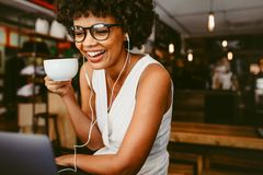 Lycklig kvinna p? kaf?t genom att anv?nda b?rbara datorn royaltyfri bild