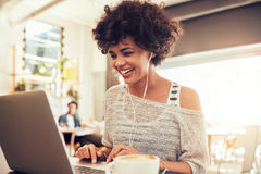 Lycklig kvinna på kafét genom att använda bärbara datorn Fotografering för Bildbyråer
