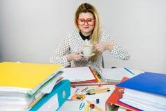 Lycklig kvinna p? kontoret som dricker varmt kaffe arkivfoto