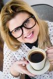 Lycklig kvinna p? kontoret som dricker varmt kaffe royaltyfria bilder