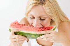Lycklig kvinna som äter den nya vattenmelon Fotografering för Bildbyråer