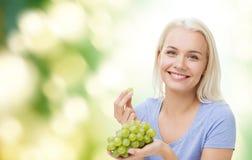 Lycklig kvinna som äter druvor arkivbilder