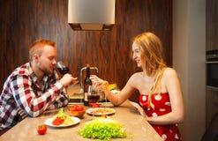 Lycklig kvinna som äter förflutnaerna medan manavsmakningvin royaltyfria foton