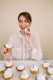 Lycklig kvinna som äter muffin på tabellen och har gyckel Arkivfoto