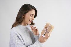 Lycklig kvinna som öppnar gåvan i studioskott arkivfoton