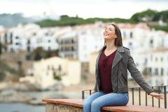 Lycklig kvinna som andas ny luft på en avsats i en stad royaltyfria foton