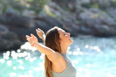 Lycklig kvinna som andas ny luft som lyfter armar på ferier Arkivfoton