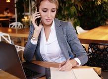 Lycklig kvinna som använder att prata med mobilen och bruksbärbar datordatoren Royaltyfria Bilder