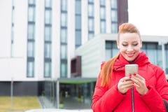 Lycklig kvinna som använder att smsa på den smarta telefonen utomhus på en stadsbyggnadsbakgrund arkivfoto