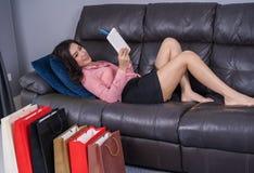 Lycklig kvinna som använder den digitala minnestavlan för online-shopping med kreditering arkivbild