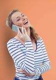 Lycklig kvinna som använder den smarta telefonen över persikabakgrund Royaltyfria Foton