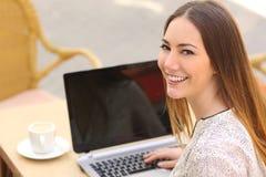 Lycklig kvinna som använder en bärbar dator i en restaurang och ser kameran