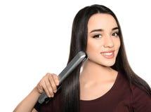 Lycklig kvinna som använder hårjärn på vit royaltyfri foto