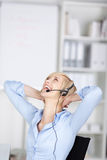 Lycklig kvinna som använder hörlurar med mikrofon Royaltyfri Fotografi
